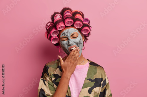 Tired exhausted woman yawns and wants to sleep applies beauty mask for having smooth skin makes perfect hairstyle with curlers dressed in casual domestic clothing isolated over pink background