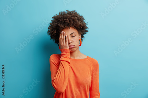 Fototapeta Exhausted unhappy woman makes face palm and sighs from tiredness has sleepy expression fed up of working without rest wears orange jumper in one color with earrings