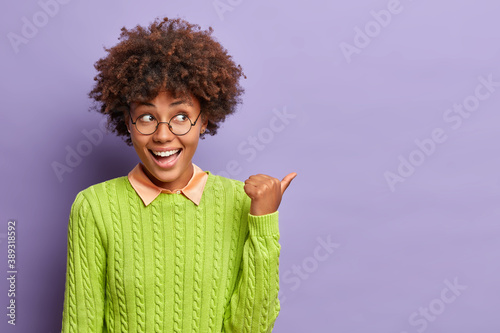 Fototapeta Happy good looking ethnic woman with Afro hair points away on blank space shows place for your advertising content or commercial text dressed in casual jumper isolated over purple backround. obraz