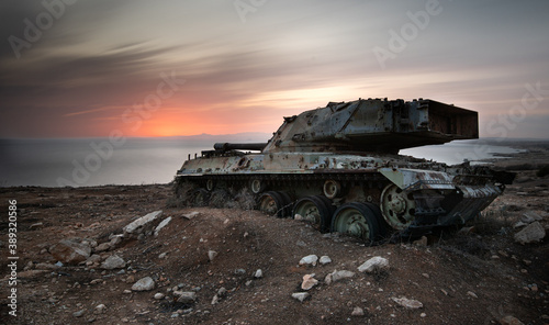 Fotografering Old rusty abandoned military tank at sunset