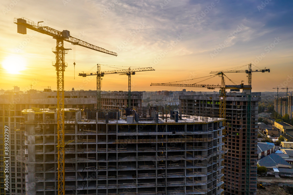 Fototapeta Construction site with cranes at sunset. Construction of an apartment building