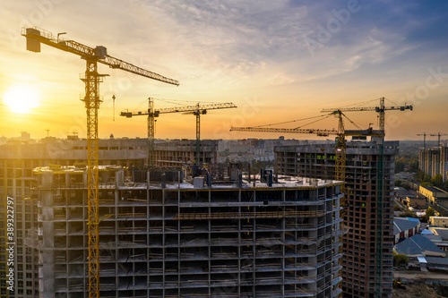 Foto Construction site with cranes at sunset
