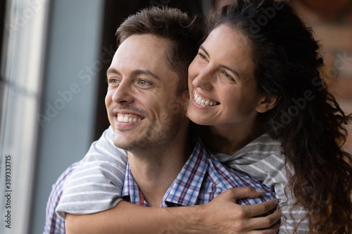 Canvas Print Close up of excited young Caucasian couple hug look in distance dreaming or thinking happy bright future together