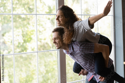 Obraz Excited young Caucasian woman piggyback man spouse feel playful relocate to new own house together. Happy millennial couple renters or tenants have fun relax on family leisure weekend at home. - fototapety do salonu