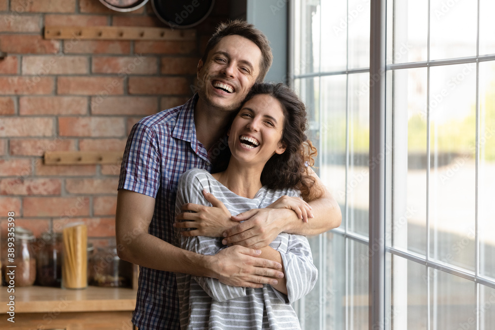 Fototapeta Portrait of overjoyed millennial man and woman hug cuddle excited to move to new own shared apartment together. Smiling young Caucasian couple embrace enjoy family weekend at home. Rental concept.