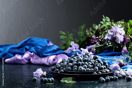 Summer still life with blueberries, colored sweet peas and meadow grasses on a dark blue table Canvas