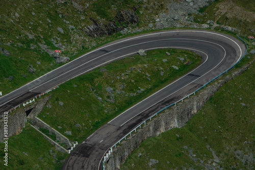 Detail of a curve on epic winding road on Transfagarasan pass in Romania in summer time, with twisty road rising up Fotobehang