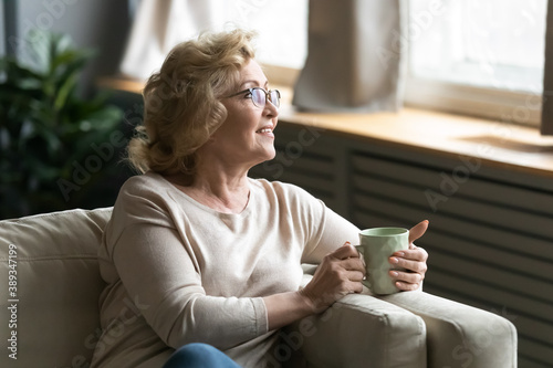 Valokuvatapetti Peaceful older senior granny in eyeglasses relaxing on coffee with cup of tea coffee in hands, dreaming of future or recollecting memories alone at home, happy retired woman enjoying morning ritual