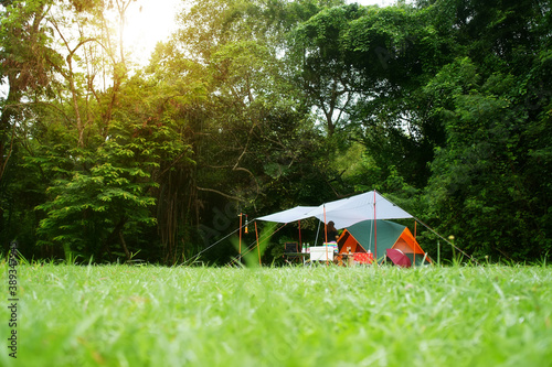 Foto nature landscape camping tent and camper with tarp or flysheet under tree on gre