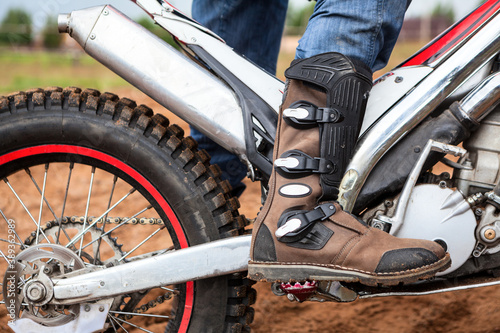 Tela Close up view at rider's motocross boot standing on peg of dirt motorcycle