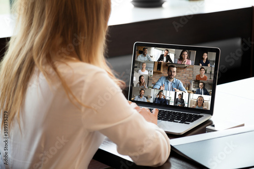 Obraz Close up rear view businesswoman talking with diverse colleagues online, using webcam, laptop, multiracial business people making video call from home, engaged in internet conference, briefing - fototapety do salonu
