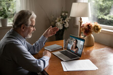 Mature Man Wearing Glasses Making Video Call To Adult Daughter, Talking, Chatting Online, Senior Teacher Mentor Teaching Student, Explaining, Working At Home, Using Laptop And Social Media App