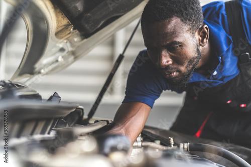 Black male mechanic repairs car in  garage Billede på lærred