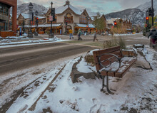 Evening View Of A Street Bench, Pedestrians And Stores On Banff Avenue In Banff, Alberta, Canada