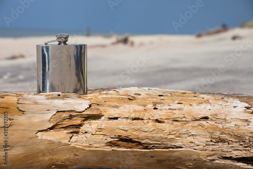 Obraz Hip flask on a wooden beam lying on the beach. - fototapety do salonu