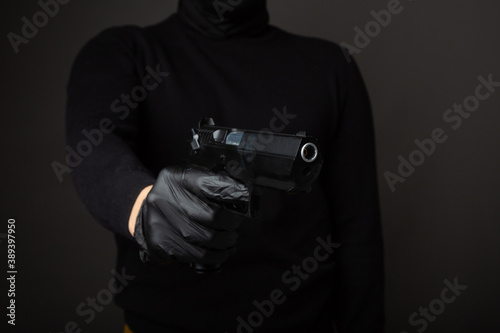 Fotografia a gun in the hands of a robber on a black background
