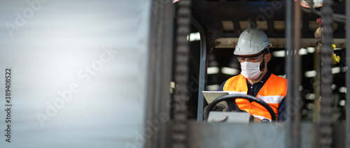 Fotografie, Obraz Young male staff driving forklift in warehouse