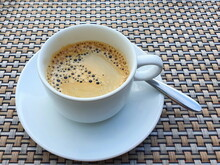 A Cup Of Espresso With Delicate Foam Lather Floats On Top. Served On A Coaster With A Stainless Steel Spoon For Coffee Stir. Americano Is Hot, Fresh, Delicious, Tastes Just Right.
