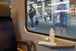 New normal commuting and traveling with face masks and hand sanitizers displayed in train carriage. Train is at station and the passengers wearing face masks go in trying to keep social distance.