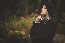 Woman In Black Cloak And Hat With Vintage Camera In Outdoor