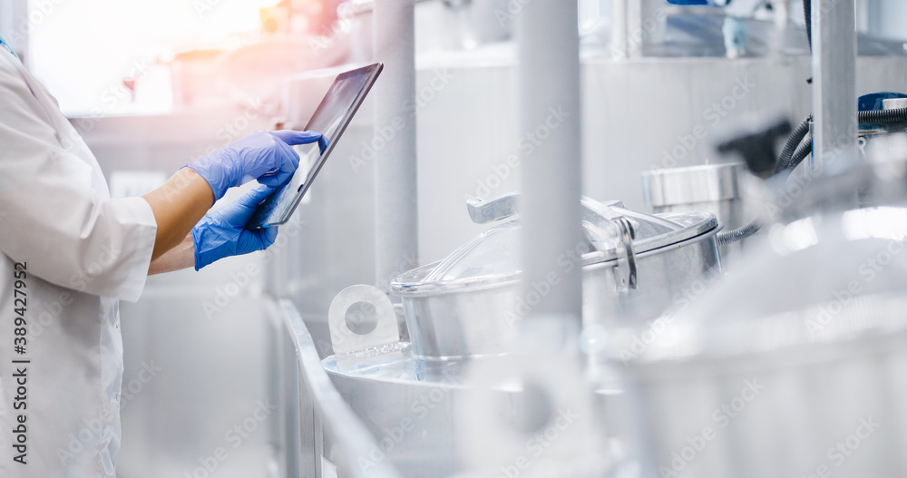 Fototapeta Concept food industry banner. Factory worker inspecting production line tanker in of dairy factory with computer tablet