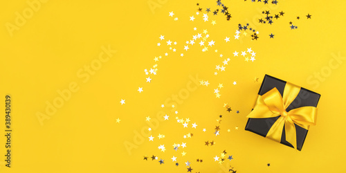 Obraz na plátně Black gift box with yellow bow on yellow background with sparkling confetti