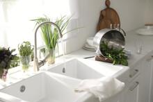 Colander With Fresh Spinach On Countertop Near Sink In Kitchen