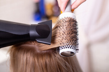 Female hairdresser's hand brushing and blow drying blonde hair in beauty salon