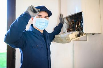 Obraz na płótnie Canvas Smiling technician repairing an hot-water heater wearing a mask, coronavirus concept