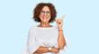 canvas print picture - Beautiful middle age mature woman wearing casual clothes and glasses with a big smile on face, pointing with hand and finger to the side looking at the camera.