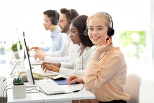 Team Of Diverse Hotline Operators With Headphones Providing Service To Clients At Call Center
