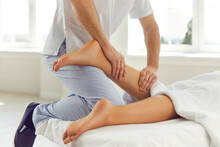 Physiotherapist Or Reflexologist Massaging Young Woman's Calf Muscle In Wellness Center