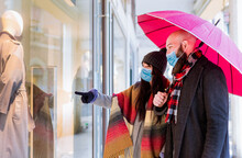 Beautiful Couple With An Umbrella And Winter Clothes Is Talking And Smiling While Doing Shopping In The City In A Rainy Day.side View Of A Couple Walking Past A Shop Window And Looking In For Sales .