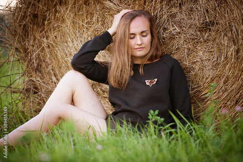 Fotografija woman in a black sweater with a handmade brooch sits the the field