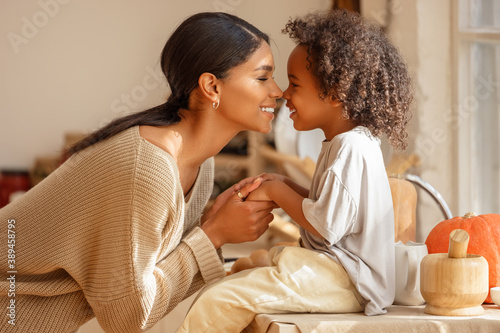 Foto Happy ethnic family mother and   son kiss and laugh in the kitchen at home