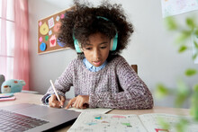 Cute Focused African School Kid Girl Wearing Headphones Virtual Distance Learning Online Listening Remote Education Digital Class Doing Homework Studying At Home Classroom Sitting At Desk With Laptop.