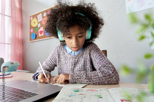 Cute focused african school kid girl wearing headphones virtual distance learning online listening remote education digital class doing homework studying at home classroom sitting at desk with laptop Fototapeta