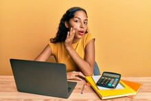Young African American Girl Working At The Office With Laptop And Calculator Hand On Mouth Telling Secret Rumor, Whispering Malicious Talk Conversation