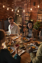 Vertical Portrait Of Cheerful Adult People Sitting At Dinner Table While Enjoying Party With Outdoor Lighting