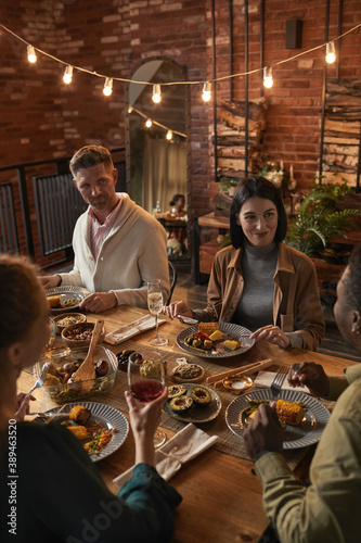 Fototapeta Vertical portrait of cheerful adult people sitting at dinner table while enjoying party with outdoor lighting obraz na płótnie