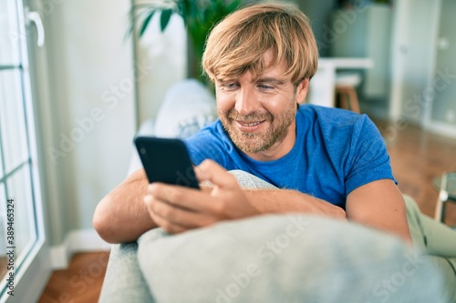 Obraz Middle age handsome caucasian man relaxing at sitting on the sofa at home with smartphone - fototapety do salonu