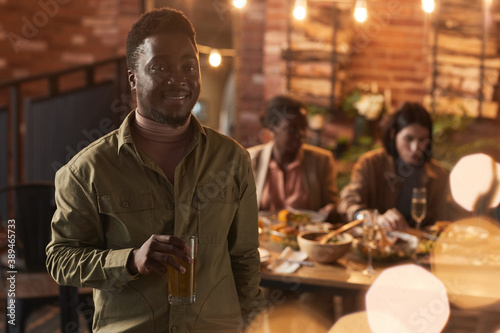 Fototapeta Waist up portrait of smiling African-American man holding champagne glass and looking at camera while enjoying party outdoors, copy space obraz na płótnie