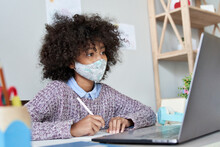 African American School Kid Child Girl Wearing Face Mask Watching Online Class Live Stream Lesson Virtual Distance Learning Remote Education Looking At Laptop Computer Studying At Home Classroom Desk.