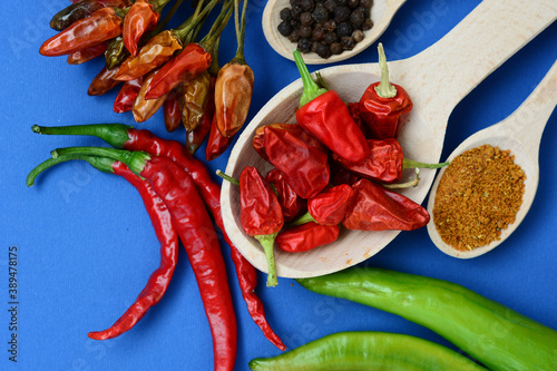 Fotografiet chili pepper, various spices on old wooden - top view