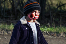 A Three Year Old Boy Dresses Up As A Zombie For Halloween Posing On A Rural Road In Ontario Canada At Sunset.  A Spooky Apocalyptic Scene.