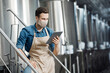 Busy millennial attractive man in apron and protective mask uses tablet to control brewery with mobile app