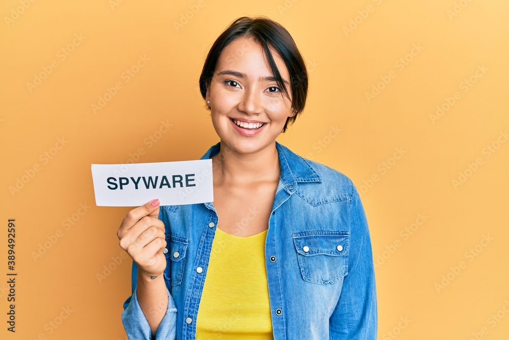 Fototapeta Beautiful young woman with short hair holding spyware text looking positive and happy standing and smiling with a confident smile showing teeth