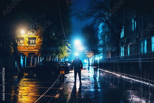 Silhouette of alone stranger in hood at night city street in rain Fototapeta