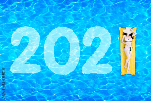 Woman lying on inflatable float with number 2021 Fototapeta