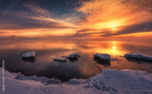 Fototapeta Rocks in the lake during frozen winter month before the sunrise obraz